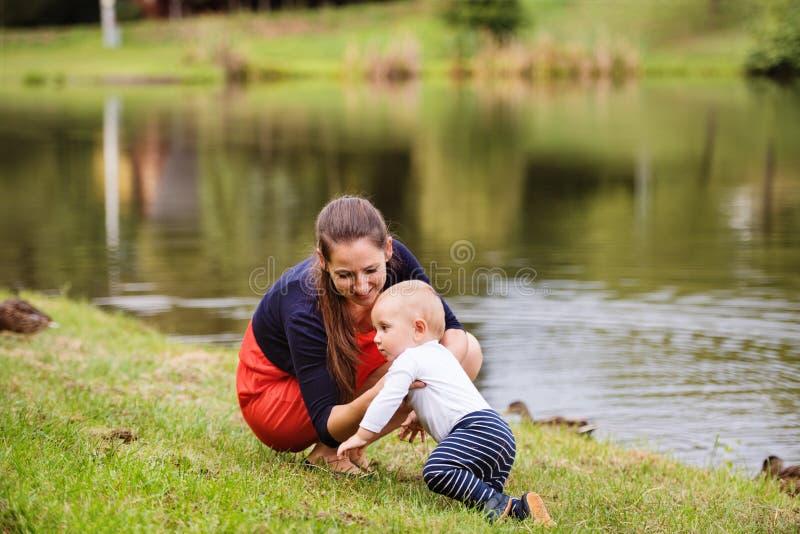 Kleiner Junge mit seiner Mutter, die erste Schritte macht stockfotografie
