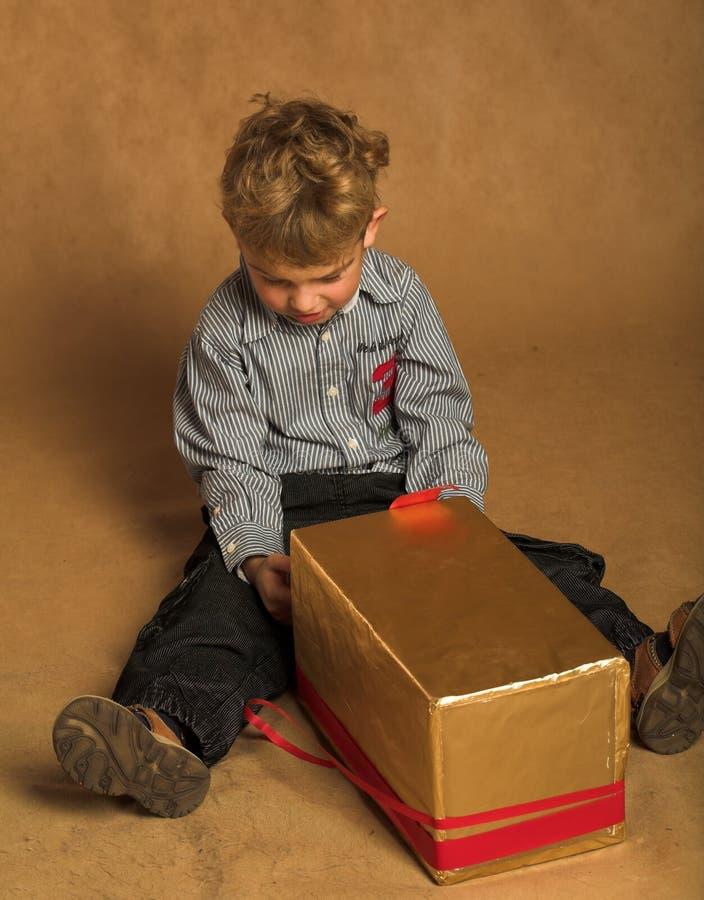 Kleiner Junge mit Weihnachtsgeschenk lizenzfreie stockfotografie