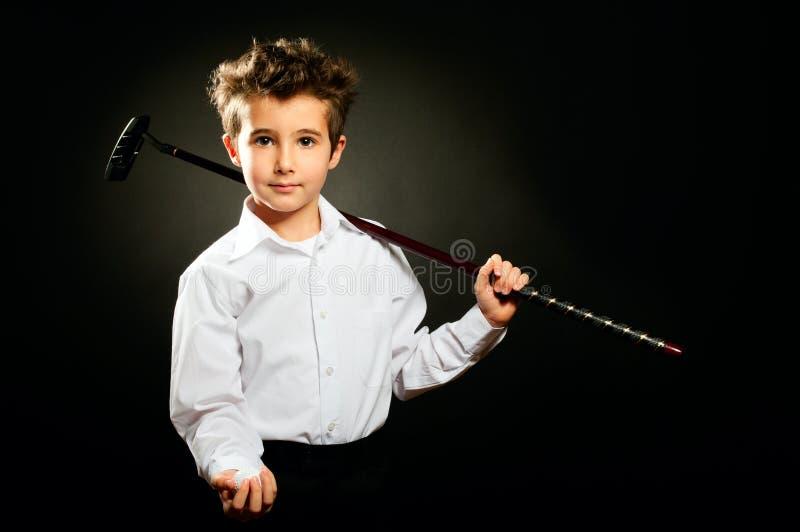 Kleiner Junge mit zurückhaltendem Studioporträt des Golfclubs lizenzfreies stockbild