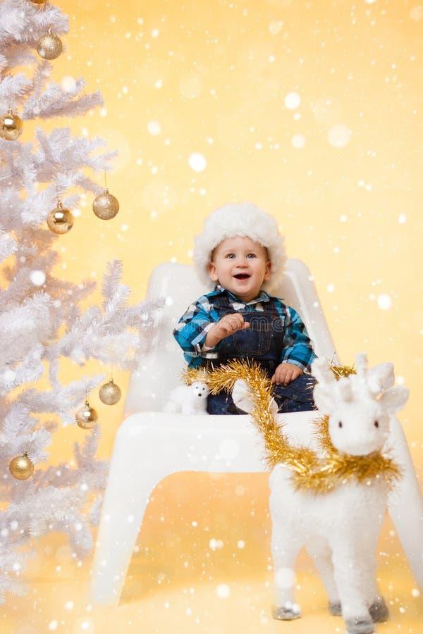 Kleiner Junge nahe Weihnachtsbaum genießt den Schnee im Lastwagen mit einem Spielzeugrotwild stockfoto