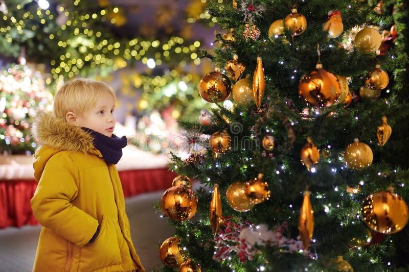Kleiner Junge nahe Weihnachtsbaum goldene Bälle draußen verzierend lizenzfreie stockbilder