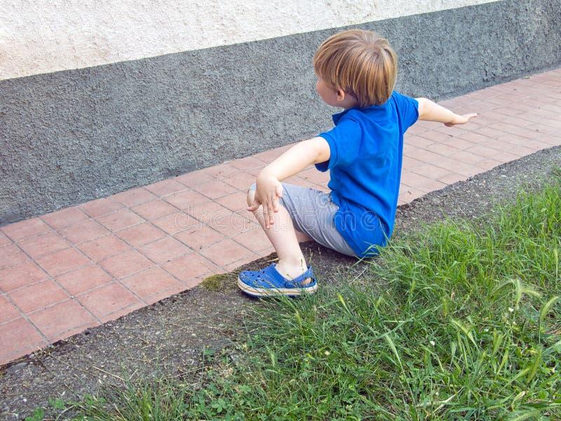 Kleiner Junge saß auf Gartenwand, die ausgestreckten Arme Draußen spielen stockbilder