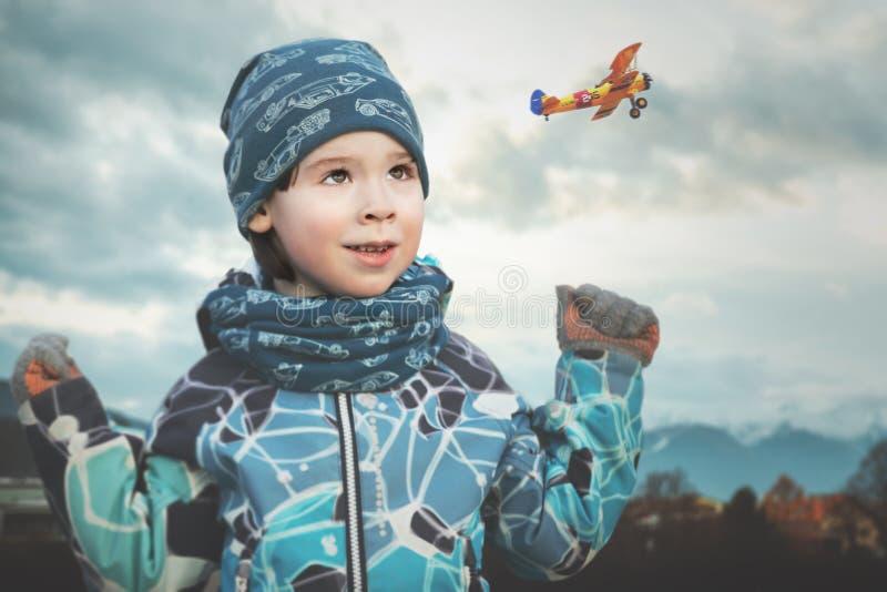 Kleiner Junge schaut zum kleinen Flugzeug im blauen Himmel, um Traumfliege zu lassen lizenzfreie stockfotografie