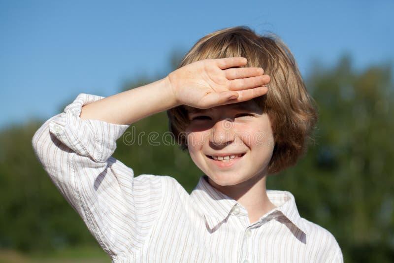 Kleiner Junge schließt seine Hand von der Sonne lizenzfreies stockfoto