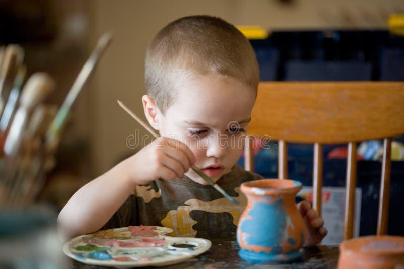 Kleiner Junge schmerzt das Lehmglas lizenzfreie stockfotos