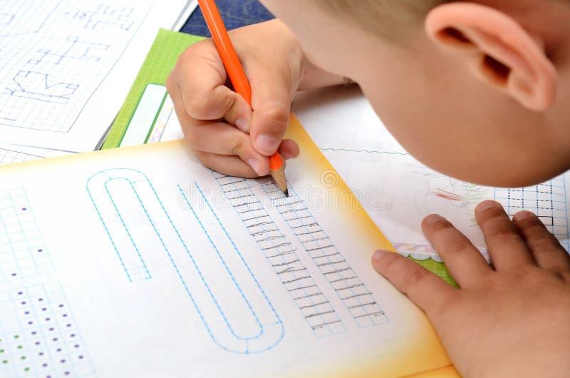 Kleiner Junge schreibt mit Sorgfalt mit einem Bleistift in sein Notizbuch lizenzfreie stockfotografie