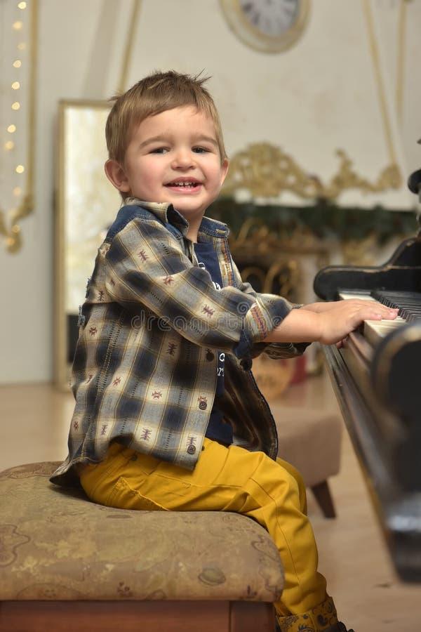 kleiner Junge, sitzend auf Stuhl und spielen auf Klavier lizenzfreies stockfoto