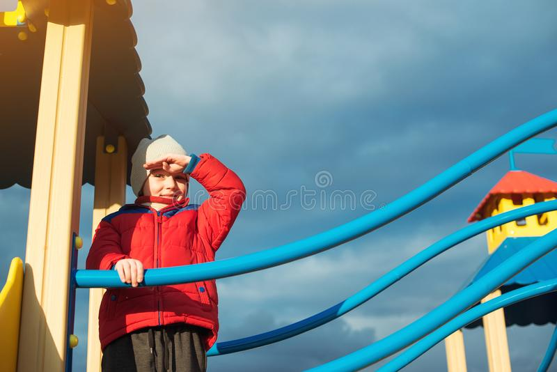 Kleiner Junge spielt am Freienspielplatz am kalten Tag Glückliche Kindheit Moderner bunter Spielplatz auf Hintergrund des bewölkt stockfotografie