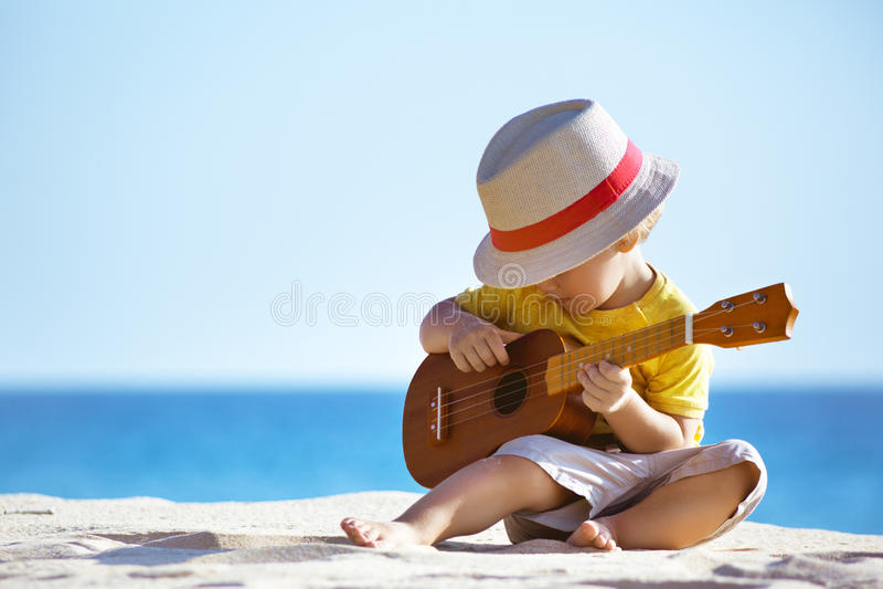 Kleiner Junge spielt Gitarrenukulele am Seestrand lizenzfreie stockfotografie