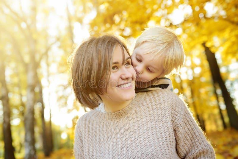 Kleiner Junge umfasst seine Mutter und das Küssen sie während des Spaziergangs am sonnigen Herbstpark stockbild