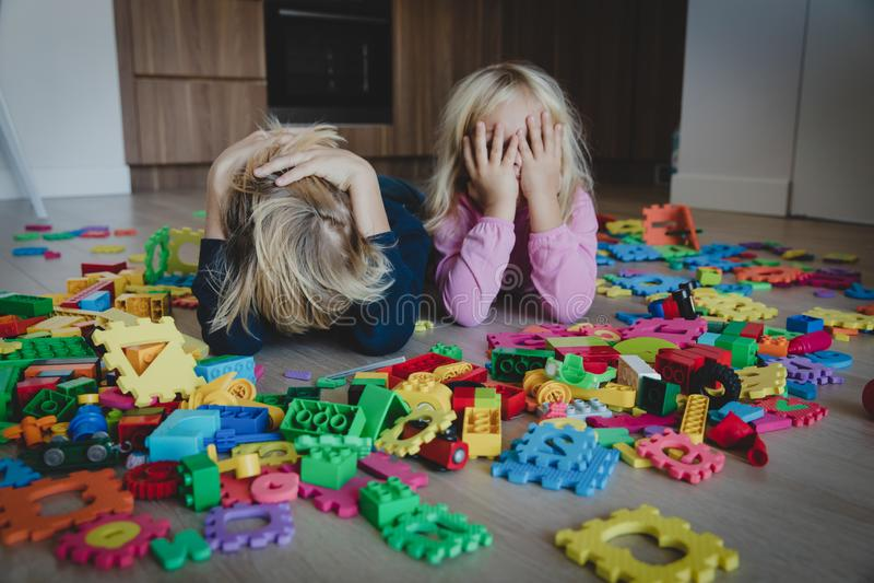 Kleiner Junge und das Mädchen, die ermüdet war, betonten erschöpft mit den Spielwaren, die zuhause zerstreut wurden lizenzfreies stockfoto