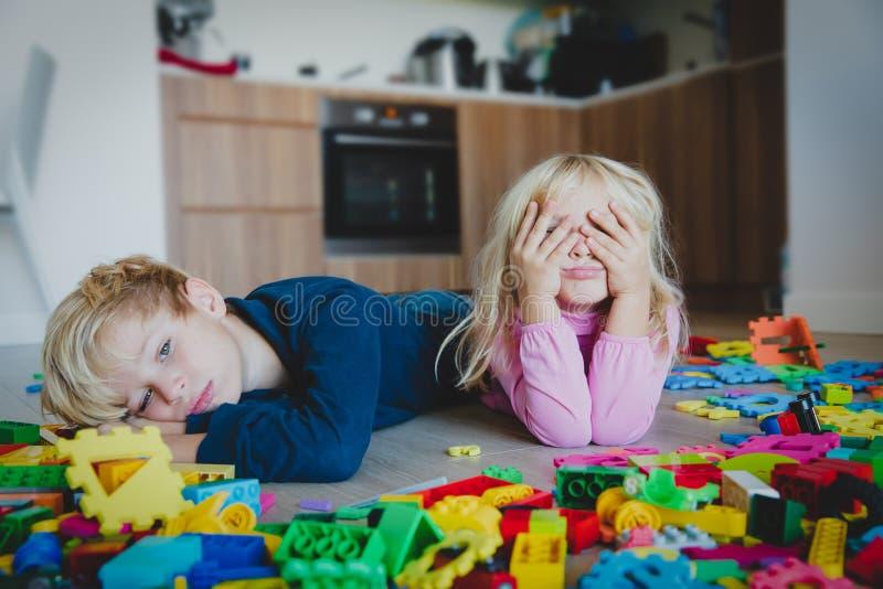 Kleiner Junge und das Mädchen, die ermüdet war, betonten erschöpft mit den Spielwaren, die zuhause zerstreut wurden lizenzfreie stockfotografie