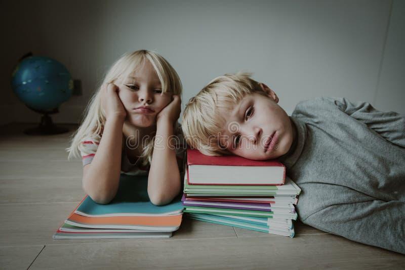 Kleiner Junge und das Mädchen gebohrt müde betonten vom Handeln von Hausarbeit stockbilder