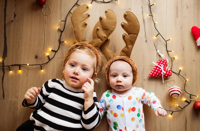 Kleiner Junge und Mädchen auf dem Boden zur Weihnachtszeit stockfotografie