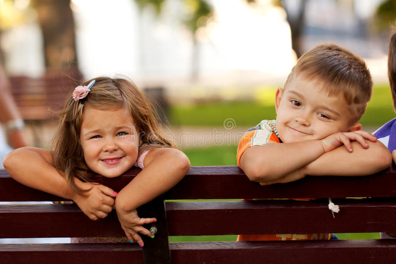 Kleiner Junge und Mädchen auf einer Bank stockfotos