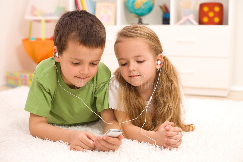 Kleiner Junge und Mädchen, die Musik hört stockfotos