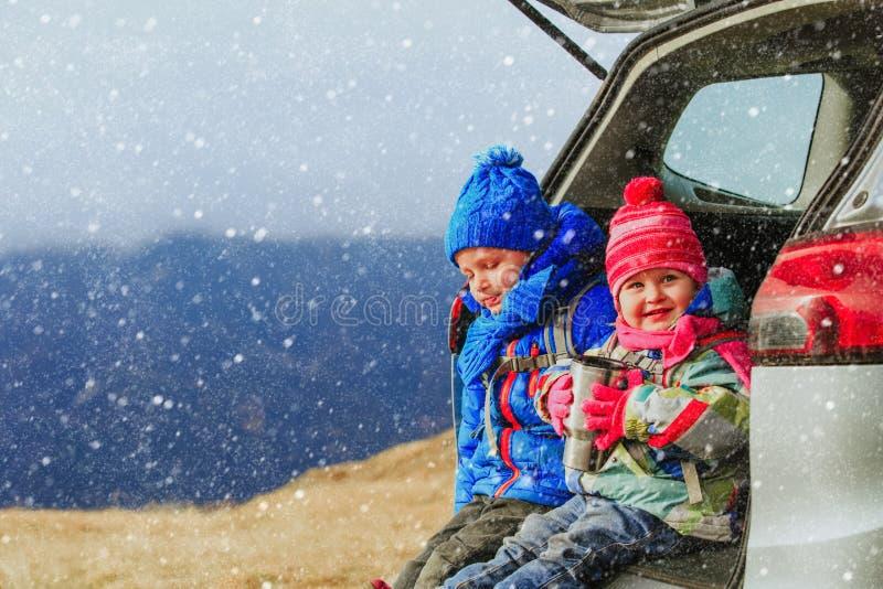 Kleiner Junge und Mädchen reisen mit dem Auto in Winterberge stockfotos