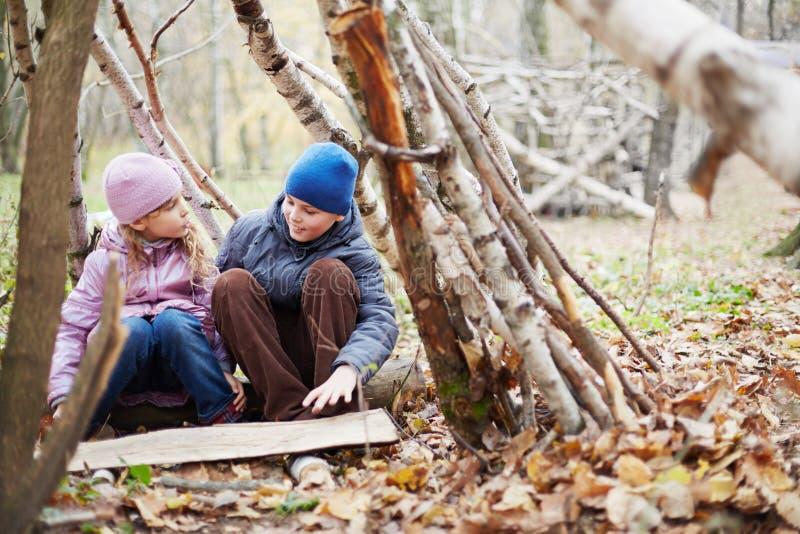 Kleiner Junge und Mädchen sitzen in der Hütte, die zwischen Birken errichtet wird stockbild