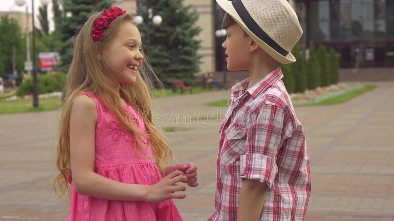 Kleiner Junge und Mädchen sprechen draußen stockbild