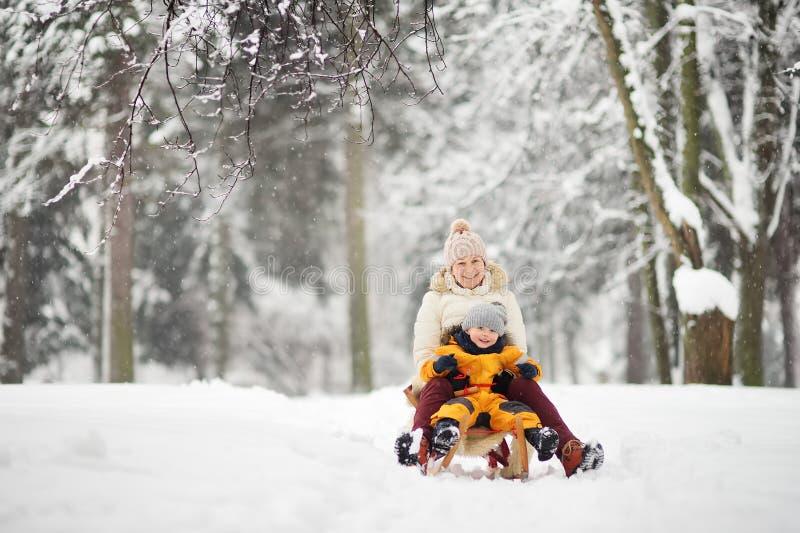 Kleiner Junge und Mutter/Großmutter/Kindermädchen, das in den Park während Schneefälle schiebt stockbilder