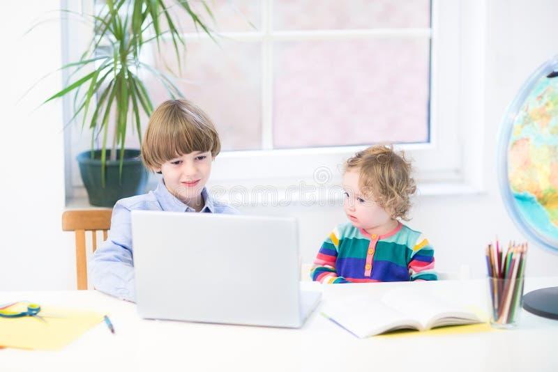 Kleiner Junge und seine nette Kleinkindschwester mit Laptop stockfoto