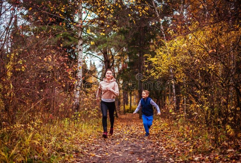 Kleiner Junge und seine Schwester, die in Herbstwald läuft stockbilder