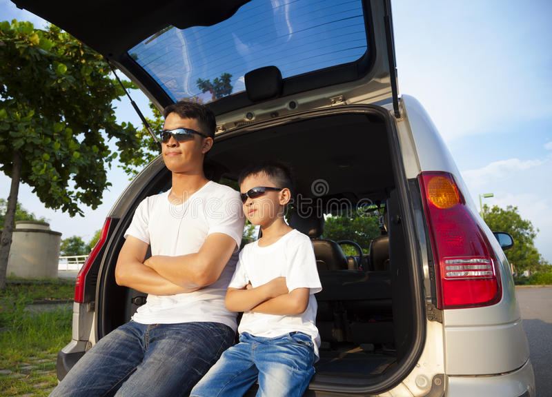 Kleiner Junge und Vater, die auf ihrem Auto sitzt lizenzfreie stockbilder