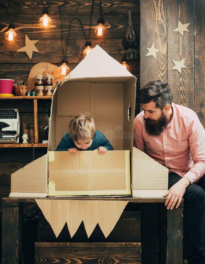 Kleiner Junge und Vater im kleinen Jungen der Papierrakete und Vater spielen mit Rakete und dem Träumen über zukünftige Karriere stockfotografie