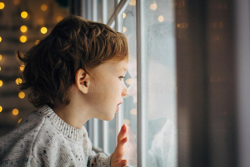 Kleiner Junge Warteweihnachtsmann Netter gelockter Kleinkindjunge, der nahe dem Fenster sitzt lizenzfreies stockfoto