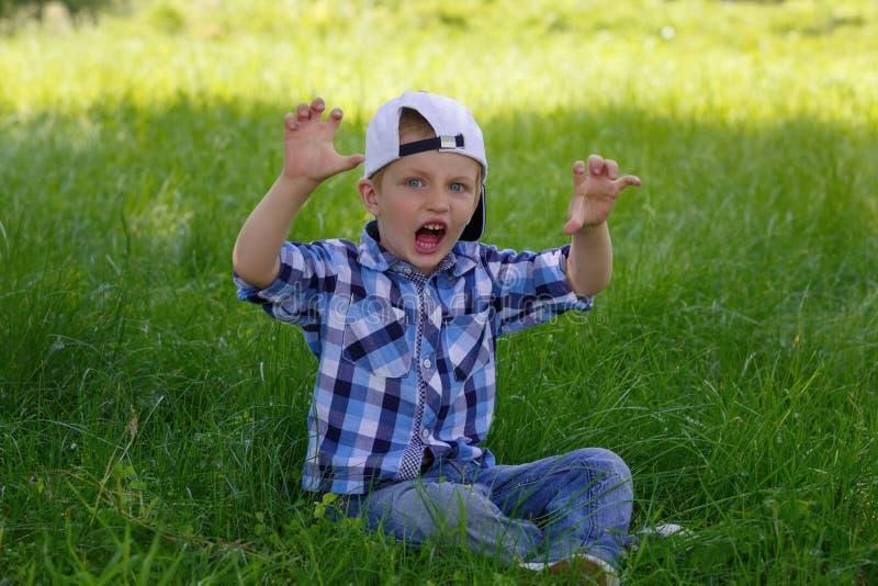 Kleiner Junge zeigt einen Knurrentiger stockfoto