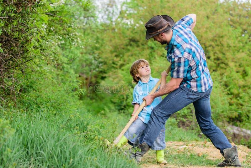 kleiner Jungenkinderhilfsvater bei der Landwirtschaft reicher Untergrund Eco-Bauernhof ranch Stammbaum pflanzendes des Vaters und stockbild