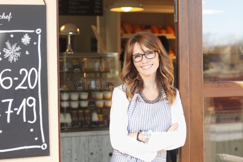 Kleiner Kaffeestubeinhaber, der vor Speicher steht. lizenzfreie stockfotos