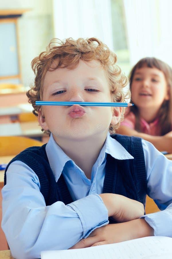 Kleiner kaukasischer gelockter Schüler hat Spaß zwischen Lektionen in der Grundschule lizenzfreies stockbild