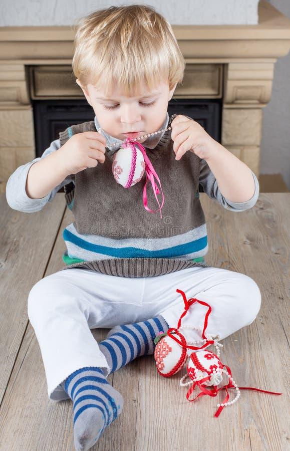 Kleiner Kleinkindjunge, der mit selbst gemachten Ostereiern spielt stockfotografie