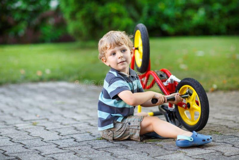 Kleiner Kleinkindjunge, der sein erstes Fahrrad repariert lizenzfreie stockbilder