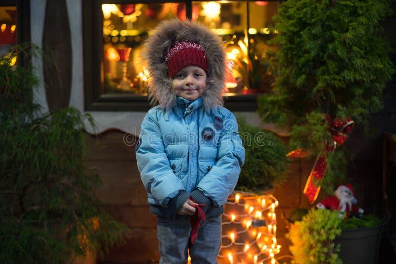 Kleiner Kleinkindjunge, der zur Weihnachtszeit und mit bunten Lichtern vom Weihnachtsbaum auf Hintergrund im Freien steht lizenzfreies stockfoto