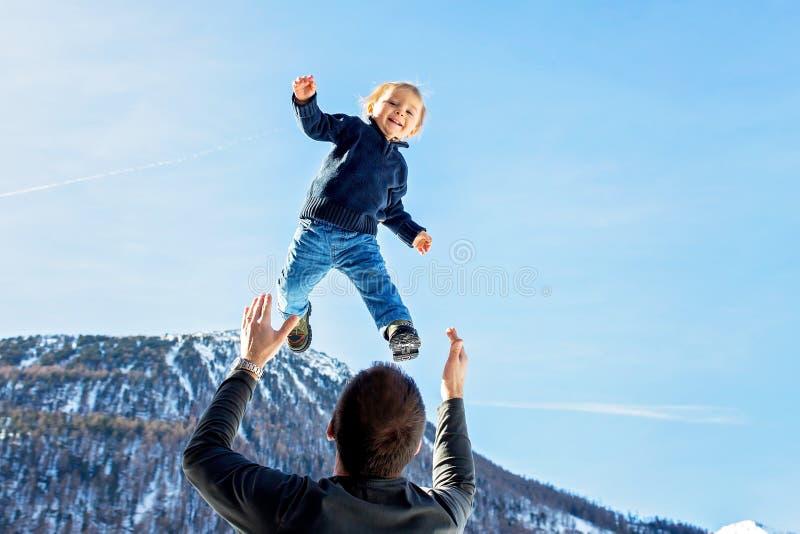 Kleiner Kleinkindjunge, fliegend in den Himmel, Vati, der ihn hoch in der Luft wirft Familie, Winteransicht von schneebedeckten B stockfotos