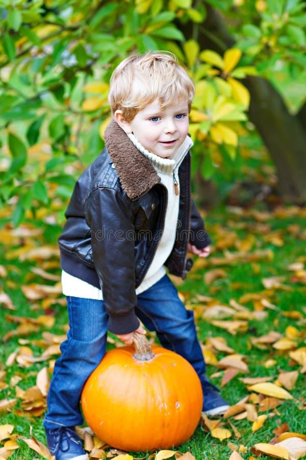 Kleiner Kleinkindkinderjunge mit großem Kürbis im Garten lizenzfreies stockbild