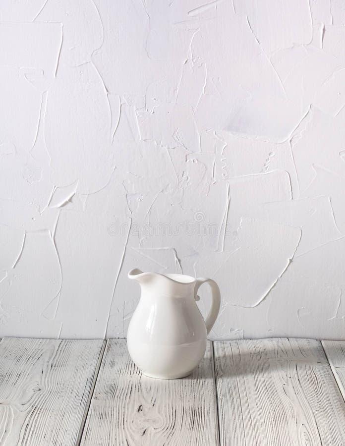 kleiner Krug für dienende Creme auf einer Tabelle auf einem weißen Holztisch stockfotos
