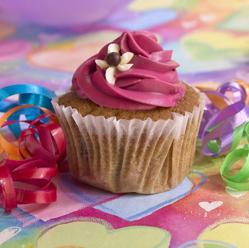 Kleiner Kuchen mit dunkler rosa Creme auf einem farbigen Hintergrund lizenzfreie stockfotografie