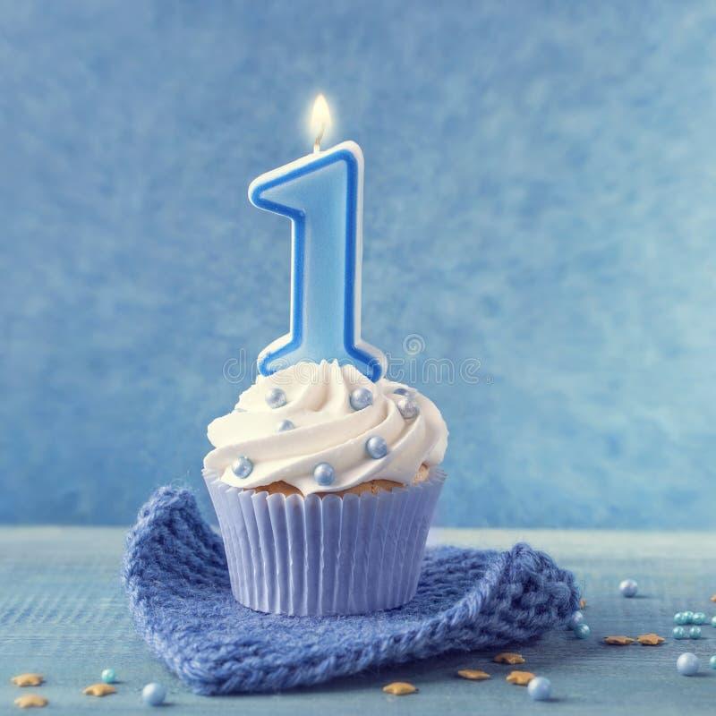 Kleiner Kuchen mit einer blauen Kerze stockfotos