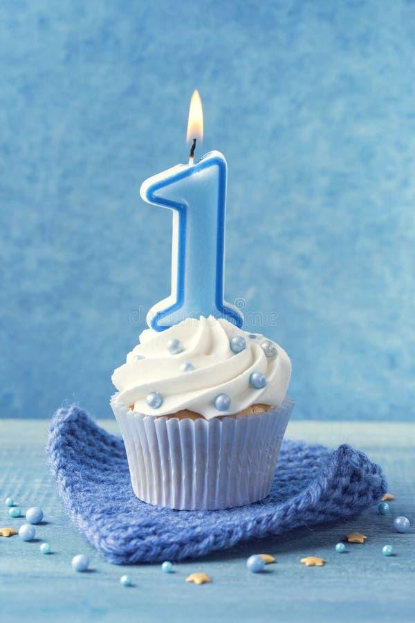 Kleiner Kuchen mit einer blauen Kerze lizenzfreie stockfotos