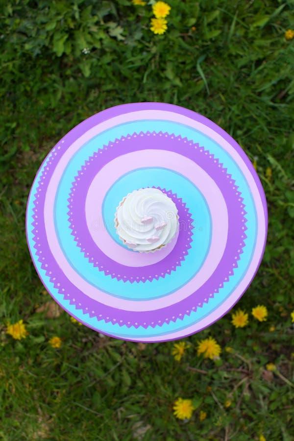 Kleiner Kuchen mit Sahne auf bunter Tabelle stockfoto