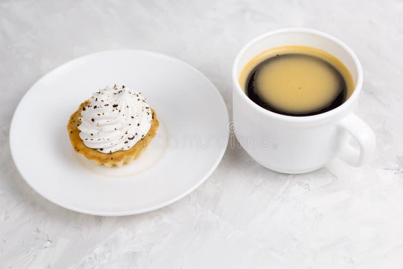 kleiner Kuchen mit Sahne verziert mit Schokoladensplittern und Kaffeecu stockbild