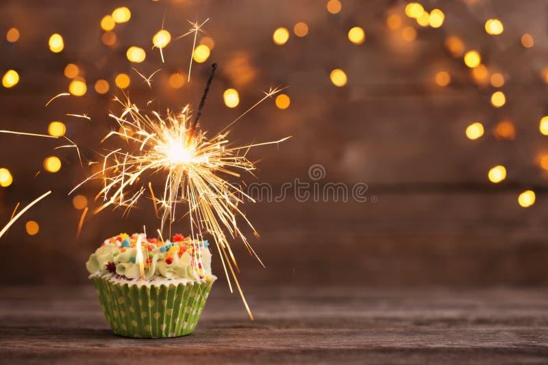 Kleiner Kuchen mit Wunderkerze auf altem hölzernem Hintergrund stockfoto