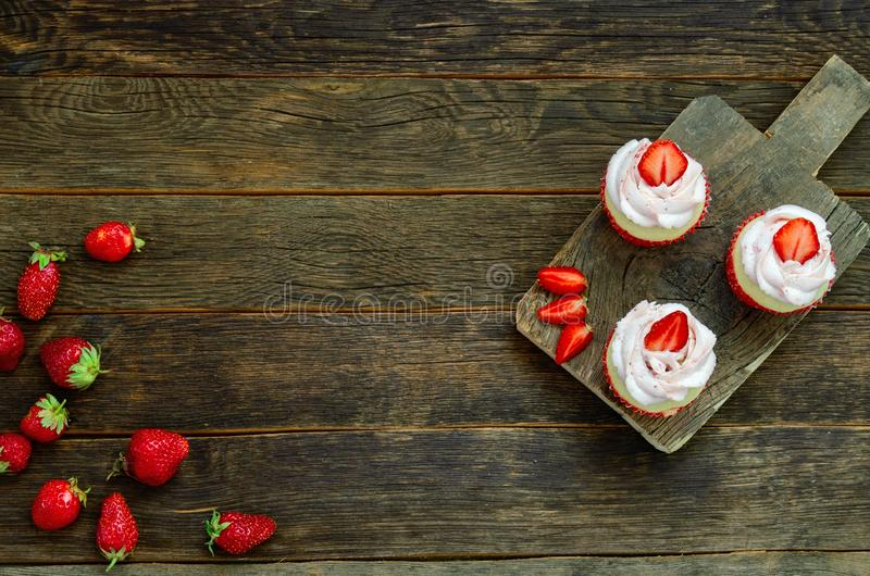 Kleiner Kuchen mit Wunderkerze auf Tabelle auf hölzernem Hintergrund lizenzfreie stockfotos