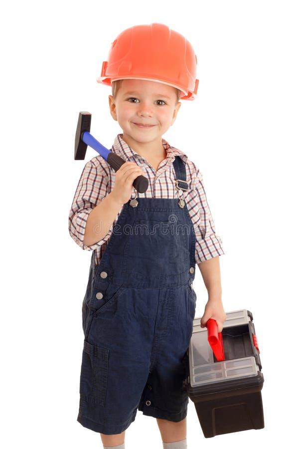 Kleiner lächelnder Erbauer mit Hammer und Werkzeugkasten lizenzfreies stockfoto