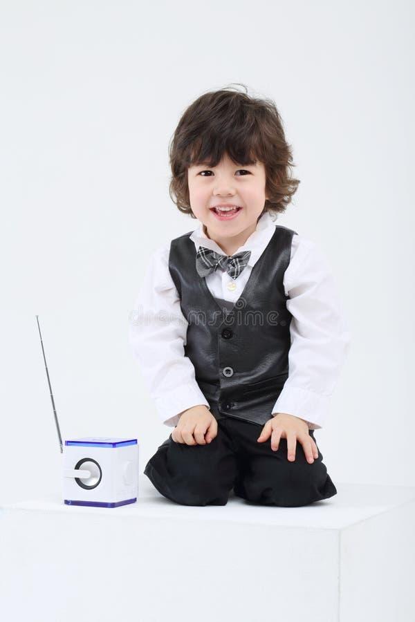 Kleiner lächelnder Junge sitzt nahe portablem Radio mit a lizenzfreies stockbild
