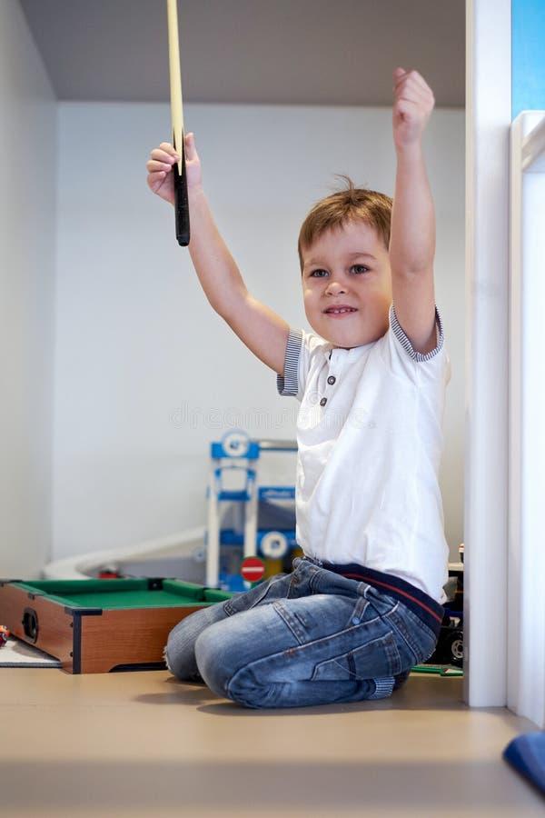Kleiner lächelnder Junge spielt auf einem Boden zu Hause im Billard stockbilder