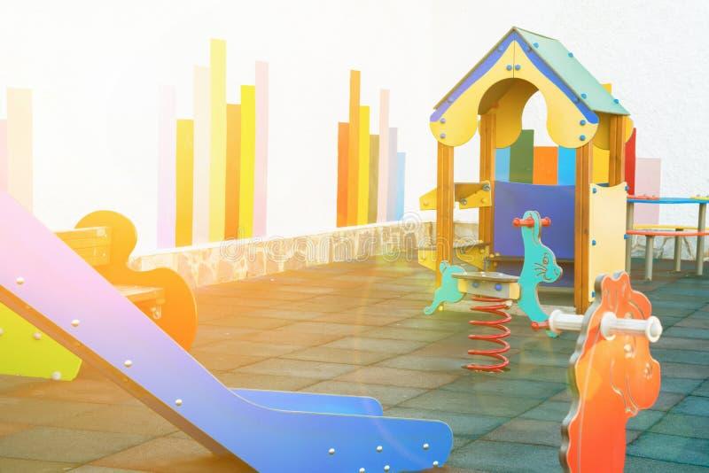 Kleiner leerer Kinderspielplatz eines Kindergartens in einer europäischen Stadt Bunter Dia-Weichgummi-Boden des Holzhaus-ständige stockfoto
